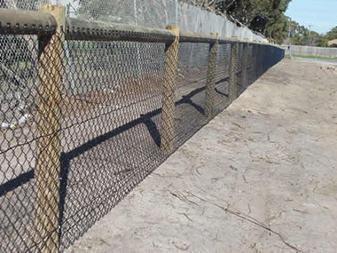 Chain mesh fence with razor wire and barbed wire.
